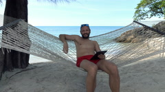 Portrait of happy man with tablet computer lying on hammock on beach Stock Footage