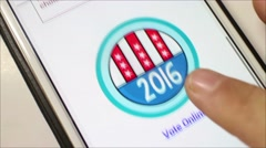 Overhead medium shot of user tapping a 2016 Voting button on smartphone Stock Footage