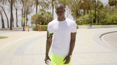 Black athlete on stone paved walkway by ocean Stock Footage