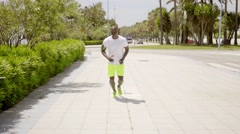 Man wearing bright yellow shorts and music device Stock Footage