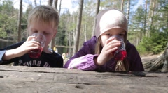 Kids drinking juice  at a camp site Stock Footage