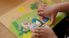 Close up of two years old child collects a fairytale picture from puzzles - stock footage