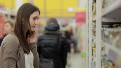 Young woman chooses canned food in the store - stock footage