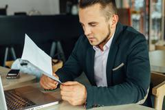 Young focused businessman sitting in cafe with laptop and analyzing documents Stock Photos