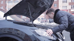 Man repairing his car on road - stock footage