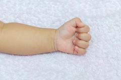 Stranglehold Hand of the baby on white diapers Kuvituskuvat