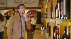 4K Attractive man choosing which wine to buy in specialist wine store - stock footage