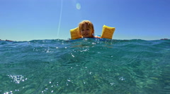 Little Girl Swimming with her Water Wings in the Sea Stock Footage