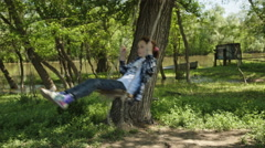 Girl in plaid shirt rides a rope swing Stock Footage
