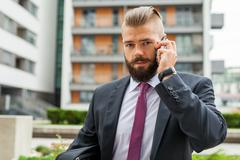 Young bearded businessman using mobile phone outside the office. Outdoor phot - stock photo
