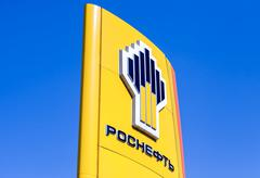 The emblem of the oil company Rosneft against the blue sky background - stock photo