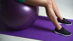 Sexy woman pumping muscles sitting on ball Stock Footage
