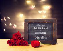 There is a always reason to smile message with roses - stock photo