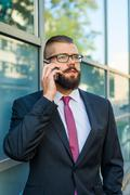 Young bearded businessman wearing eyeglasses using mobile phone outside the o - stock photo