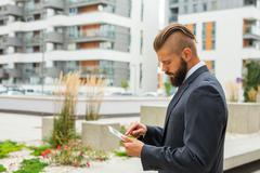Young bearded businessman writting business e-mail using his tablet pc. Outdo Stock Photos