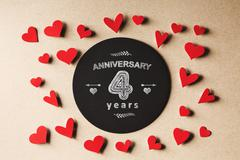 Anniversary 4 years message with small hearts - stock photo
