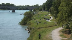 People in the distance enjoying summer on the banks of river Ticino in Pavia, Stock Footage