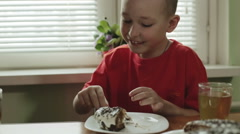 A little boy with short hair puts in his mouth a piece of cake, and drinks tea. Stock Footage