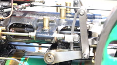 Close up of small green steam engine pumping Stock Footage