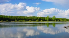 Clouds in smooth water of lake, panorama timelapse Stock Footage
