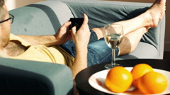 Man losing game while playing on smartphone and lying on the sofa Stock Footage