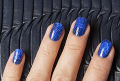 close up fingers with blue creative pattern manicure holding purse, indigo - stock photo