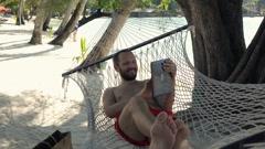 Happy man talking on tablet computer on hammock on beach, super slow motion 120f Stock Footage