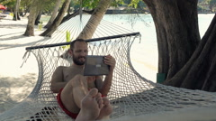Happy, young man using tablet computer on hammock on beach, super slow motion  Stock Footage
