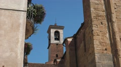 Bell tower between a flowered balcony and ancient wall in Pavia, Italy Stock Footage