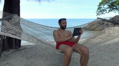 Young man using tablet computer lying on hammock on beach Stock Footage