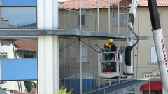 Window cleaner working on a glass facade of the building. Stock Footage