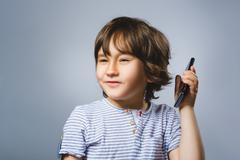 Closeup Portrait of happy boy with mobile going surprise on gray background - stock photo