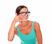 Woman gesturing calling on the phone while smiling a toothy smile and looking - stock photo