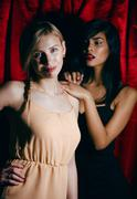 brunette and blond woman together friends, conflict of types on red curtain - stock photo