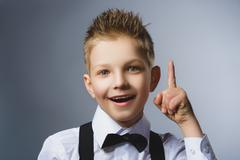 Closeup Portrait of gestured child  on grey background. Boy found the idea or Stock Photos