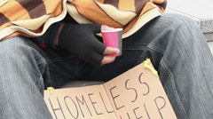 Frozen homeless man covered with blanket, begging money, holding paper cup Stock Footage