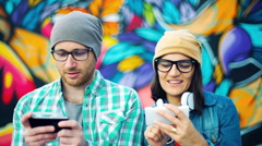 Happy hipsters using their smartphones and chatting with each other Stock Footage