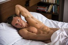 Sexy naked young man on bed Stock Photos