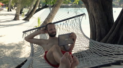 Happy man watching movie on tablet lying on hammock on beach, super slow motion  Stock Footage