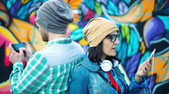 Pair of hipsters leaning on each other back and standing next to the graffiti Stock Footage