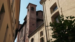 Old church with bell tower between houses and a plant in Pavia, Italy Stock Footage