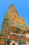 The spire of the Catholic Church in scaffolding against the blue sky Stock Photos