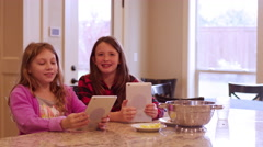 Two friends sitting at a kitchen island using their tablets Stock Footage