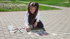 Little girl drawing on pavement with chalk - stock footage