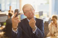 Furious businessman gesturing with fist at telephone in office - stock photo