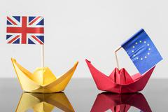 paper ship with british and european flag - stock photo