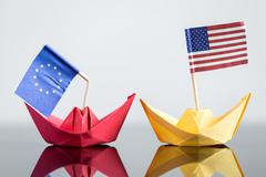 paper ship with usa and european flag - stock photo