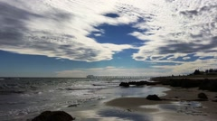 Dramatic cloudscape over deserted beach in late afternoon. Stock Footage