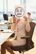Portrait of businesswoman holding frowning face printout over her face in office Stock Photos