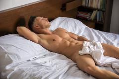 Sexy naked young man on bed - stock photo
